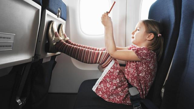 little girl on an airplane reading